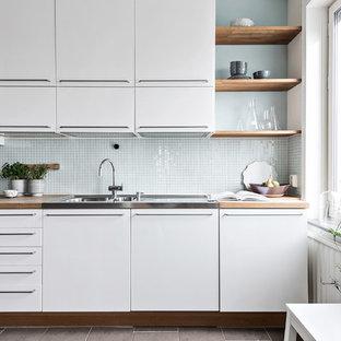 Skandinavisk inredning av ett linjärt kök, med släta luckor, vita skåp, träbänkskiva, grått stänkskydd, stänkskydd i mosaik och brunt golv