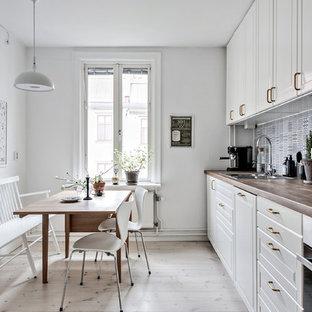 Inspiration för mellanstora nordiska linjära kök och matrum, med en dubbel diskho, vita skåp, träbänkskiva, stänkskydd i keramik, vita vitvaror, ljust trägolv, blått stänkskydd och luckor med upphöjd panel