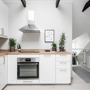Foto på ett litet nordiskt kök, med vita skåp, träbänkskiva, grått golv, en nedsänkt diskho, luckor med upphöjd panel, rostfria vitvaror och ljust trägolv