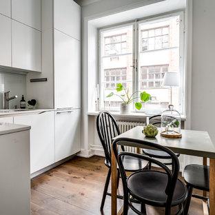 Bild på ett litet skandinaviskt kök, med en enkel diskho, släta luckor, vita skåp, integrerade vitvaror, mellanmörkt trägolv och brunt golv