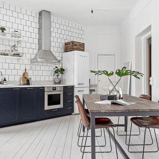 Modelo de cocina comedor lineal, nórdica, con fregadero encastrado, armarios con paneles empotrados, puertas de armario azules, salpicadero blanco, electrodomésticos blancos, suelo de madera pintada y suelo blanco
