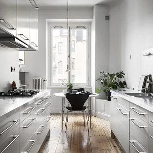Inspiration för ett minimalistiskt kök, med en dubbel diskho, släta luckor, grå skåp, ljust trägolv och beiget golv