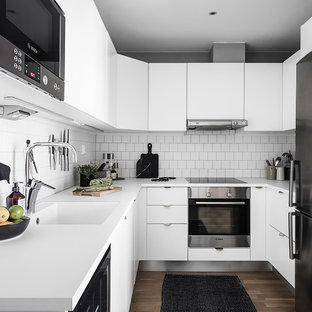 Exempel på ett litet minimalistiskt vit vitt u-kök, med en integrerad diskho, släta luckor, vita skåp, vitt stänkskydd, rostfria vitvaror, mellanmörkt trägolv och brunt golv