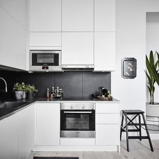 Idéer för små minimalistiska kök, med en enkel diskho, släta luckor, vita skåp, svart stänkskydd, rostfria vitvaror, ljust trägolv och beiget golv