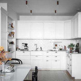 Inspiration för ett skandinaviskt vit vitt kök, med en undermonterad diskho, luckor med infälld panel, vita skåp, vitt stänkskydd, stänkskydd i tunnelbanekakel och integrerade vitvaror