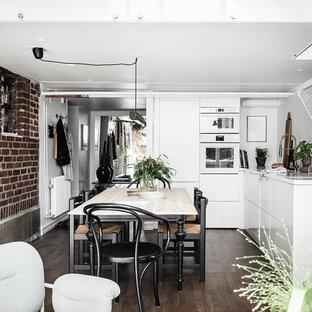 Bild på ett nordiskt vit vitt kök, med släta luckor, vita skåp, vita vitvaror, mörkt trägolv och brunt golv