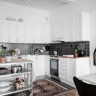 Foto på ett nordiskt flerfärgad kök, med skåp i shakerstil, vita skåp, svart stänkskydd, rostfria vitvaror, en köksö och svart golv