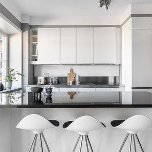 Idéer för att renovera ett skandinaviskt u-kök, med en integrerad diskho, släta luckor, vita skåp, bänkskiva i rostfritt stål, stänkskydd med metallisk yta och en halv köksö