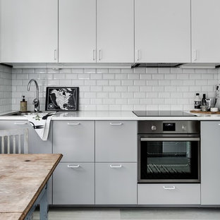 Small traditional kitchen remodeling - Small elegant l-shaped light wood floor kitchen photo in Stockholm with a single-bowl sink, flat-panel cabinets, gray cabinets, white backsplash, stainless steel appliances and an island