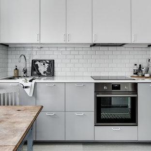 Foto på ett litet vintage l-kök, med en enkel diskho, släta luckor, grå skåp, vitt stänkskydd, rostfria vitvaror, ljust trägolv och en köksö