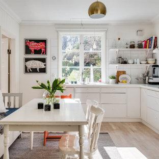Inredning av ett skandinaviskt mellanstort kök, med släta luckor, vita skåp, vitt stänkskydd, ljust trägolv och beiget golv