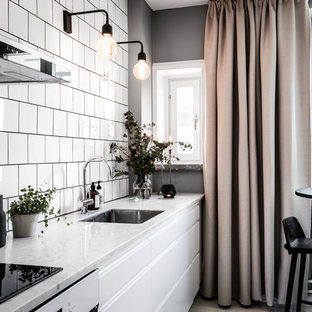 Small scandinavian open concept kitchen designs - Example of a small danish single-wall open concept kitchen design in Gothenburg with white cabinets, marble countertops, white backsplash, ceramic backsplash, stainless steel appliances and no island