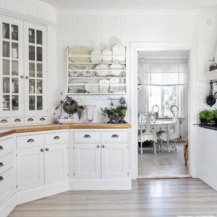 Shabby chic-inspirerad inredning av ett avskilt kök, med luckor med glaspanel, vita skåp, träbänkskiva, vitt stänkskydd, stänkskydd i tunnelbanekakel och beiget golv