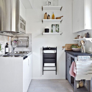 Small scandinavian kitchen photos - Example of a small danish galley light wood floor kitchen design in Stockholm with a drop-in sink, flat-panel cabinets, white cabinets, gray backsplash, stainless steel appliances and no island