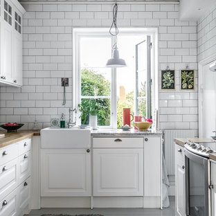 Small traditional enclosed kitchen inspiration - Enclosed kitchen - small traditional u-shaped enclosed kitchen idea in Stockholm with raised-panel cabinets, white cabinets, granite countertops, white backsplash and no island