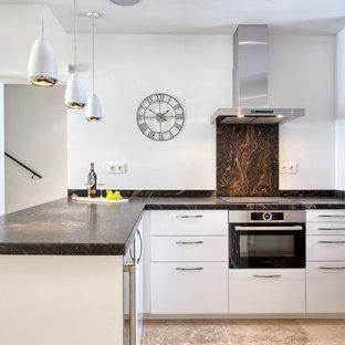 Ejemplo de cocina en L, contemporánea, de tamaño medio, abierta, sin isla, con armarios con paneles lisos, puertas de armario blancas, salpicadero blanco y electrodomésticos de acero inoxidable