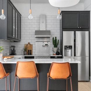 Exempel på ett mellanstort klassiskt grå grått u-kök, med en nedsänkt diskho, skåp i shakerstil, svarta skåp, vitt stänkskydd, stänkskydd i tunnelbanekakel, rostfria vitvaror, ljust trägolv, en halv köksö och beiget golv