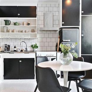 Idéer för att renovera ett mellanstort skandinaviskt kök, med en enkel diskho, släta luckor, svarta skåp, bänkskiva i rostfritt stål, vitt stänkskydd, färgglada vitvaror och målat trägolv