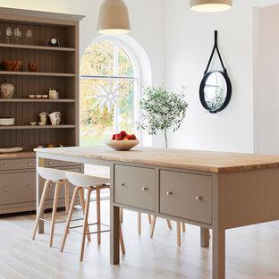 Nordisk inredning av ett mellanstort kök och matrum, med luckor med profilerade fronter, ljust trägolv, en köksö och träbänkskiva
