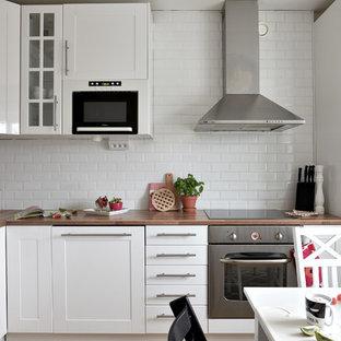 Inspiration för ett skandinaviskt brun brunt kök, med skåp i shakerstil, vita skåp, träbänkskiva, vitt stänkskydd, stänkskydd i tunnelbanekakel och rostfria vitvaror