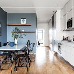 Foto på ett mellanstort funkis linjärt kök och matrum, med släta luckor, vita skåp, vitt stänkskydd, rostfria vitvaror, mellanmörkt trägolv och en nedsänkt diskho