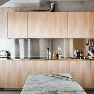 Bild på ett stort funkis linjärt kök, med släta luckor, skåp i ljust trä, bänkskiva i rostfritt stål, stänkskydd med metallisk yta, rostfria vitvaror och betonggolv