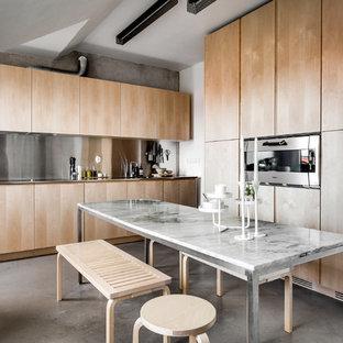 Bild på ett stort funkis kök och matrum, med betonggolv, släta luckor, skåp i ljust trä och stänkskydd med metallisk yta
