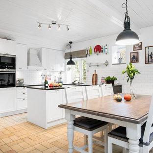 Lantlig inredning av ett stort kök, med luckor med infälld panel, vita skåp, vitt stänkskydd, svarta vitvaror, tegelgolv och en köksö