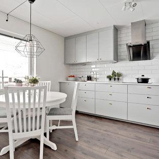 Inspiration för ett mellanstort skandinaviskt kök, med släta luckor, grå skåp, marmorbänkskiva, stänkskydd i tunnelbanekakel, svarta vitvaror, laminatgolv, brunt golv och vitt stänkskydd