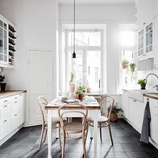 Foto på ett skandinaviskt kök, med en rustik diskho, vita skåp, träbänkskiva, vitt stänkskydd, rostfria vitvaror och svart golv