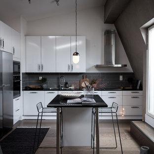 Bild på ett minimalistiskt svart svart l-kök, med en dubbel diskho, släta luckor, vita skåp, grått stänkskydd, rostfria vitvaror, mellanmörkt trägolv, en köksö och brunt golv