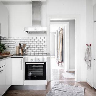 Idéer för ett skandinaviskt grå u-kök, med en integrerad diskho, släta luckor, vita skåp, bänkskiva i rostfritt stål, vitt stänkskydd, stänkskydd i keramik, vita vitvaror, mellanmörkt trägolv och brunt golv