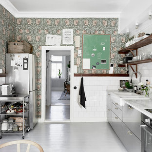 Mid-sized scandinavian single-wall kitchen in Gothenburg with a farmhouse sink, white splashback, stainless steel appliances, painted wood floors, flat-panel cabinets, stainless steel cabinets, marble benchtops and no island.