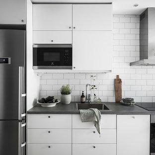 Inspiration för minimalistiska grått kök, med släta luckor, vita skåp, bänkskiva i betong, vitt stänkskydd, en nedsänkt diskho och rostfria vitvaror