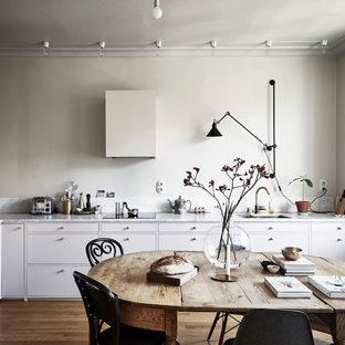 Foto på ett mellanstort nordiskt kök, med en dubbel diskho, släta luckor, vita skåp, marmorbänkskiva, grått stänkskydd, vita vitvaror och mellanmörkt trägolv