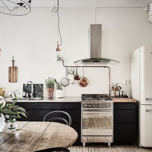 This is an example of a large industrial single-wall eat-in kitchen in Gothenburg with a double-bowl sink, flat-panel cabinets, black cabinets, stainless steel benchtops, stainless steel appliances, light hardwood floors and no island.