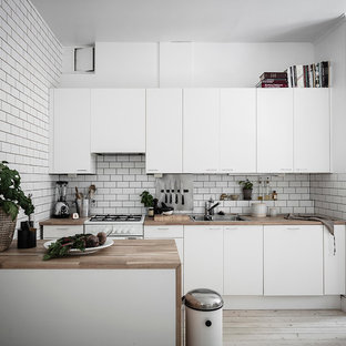 Mid-sized scandinavian single-wall eat-in kitchen in Gothenburg with flat-panel cabinets, white cabinets, white splashback, a peninsula, a double-bowl sink, wood benchtops, subway tile splashback, white appliances, painted wood floors, white floor and beige benchtop.