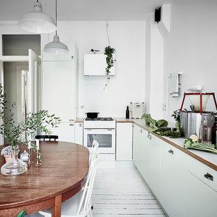Inspiration för nordiska kök och matrum, med släta luckor, gröna skåp, träbänkskiva, vitt stänkskydd, målat trägolv och vitt golv