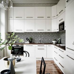 ヨーテボリの中サイズのヴィクトリアン調のおしゃれなキッチン (シングルシンク、フラットパネル扉のキャビネット、白いキャビネット、木材カウンター、シルバーの調理設備の、無垢フローリング、アイランドなし) の写真