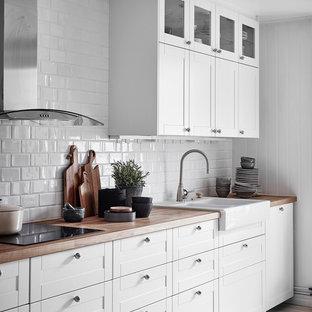 Inredning av ett skandinaviskt linjärt kök, med en nedsänkt diskho, luckor med infälld panel, vita skåp, träbänkskiva, vitt stänkskydd, stänkskydd i tunnelbanekakel, ljust trägolv och beiget golv
