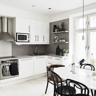 Bild på ett mellanstort nordiskt kök, med en dubbel diskho, släta luckor, vita skåp, grått stänkskydd, rostfria vitvaror och ljust trägolv