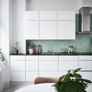 Inredning av ett skandinaviskt kök, med en undermonterad diskho, släta luckor, vita skåp, grönt stänkskydd, ljust trägolv och grått golv