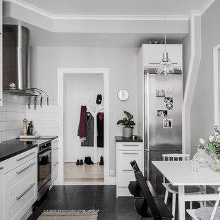 Inredning av ett nordiskt linjärt kök, med luckor med infälld panel, vita skåp, rostfria vitvaror och svart golv