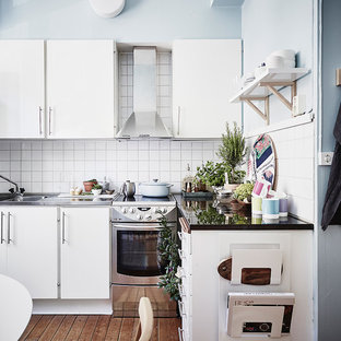 Small scandinavian eat-in kitchen photos - Small danish l-shaped medium tone wood floor and brown floor eat-in kitchen photo in Gothenburg with flat-panel cabinets, white cabinets, stainless steel countertops, white backsplash, a double-bowl sink, stainless steel appliances and no island