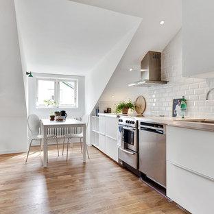 Foto på ett skandinaviskt linjärt kök och matrum, med en nedsänkt diskho, släta luckor, vita skåp, bänkskiva i rostfritt stål, vitt stänkskydd, stänkskydd i tunnelbanekakel, rostfria vitvaror och ljust trägolv