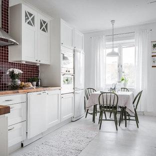 Idéer för ett skandinaviskt kök, med en nedsänkt diskho, luckor med infälld panel, vita skåp, träbänkskiva, rött stänkskydd, stänkskydd i mosaik, vita vitvaror, målat trägolv och vitt golv