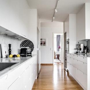 Klassisk inredning av ett mellanstort kök, med släta luckor, vita skåp, grått stänkskydd, stänkskydd i marmor, rostfria vitvaror, mellanmörkt trägolv och brunt golv