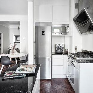 Nordisk inredning av ett mellanstort l-kök, med släta luckor, vita skåp, mörkt trägolv och en köksö