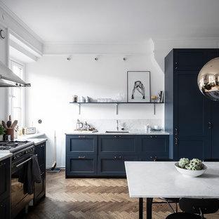 Exempel på ett stort skandinaviskt grå grått kök och matrum, med en enkel diskho, blå skåp, marmorbänkskiva, grått stänkskydd, stänkskydd i marmor, integrerade vitvaror, mellanmörkt trägolv, skåp i shakerstil och brunt golv