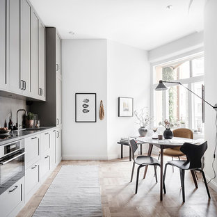 Foto på ett mellanstort nordiskt grå linjärt kök och matrum, med luckor med infälld panel, grå skåp, grått stänkskydd, en undermonterad diskho, integrerade vitvaror, mellanmörkt trägolv och beiget golv